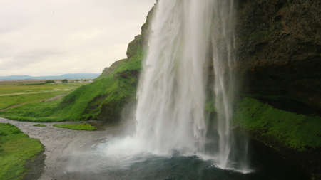 Tons of falling water from above to the ground against the green landscape of Iceland.