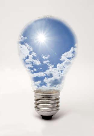 suggesting: Edison screw lightbulb containing sun and blue sky, suggesting solar energy Stock Photo