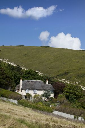 Thatched house set into hillside with blue sky photo