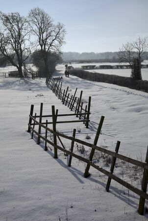 Snowy fields and old fence with family walking in background photo