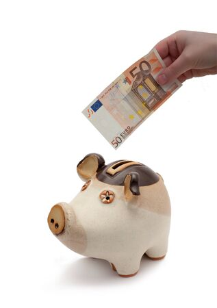 Ceramic piggy bank isolated on white background with hand inserting 50 Euro banknote photo