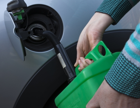 Filling petrol into car from green jerry can