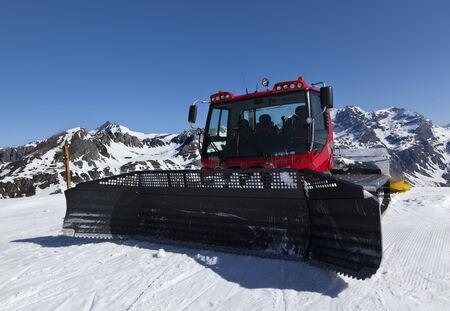 snowcat: Red piste basher parked at edge of ski run Stock Photo