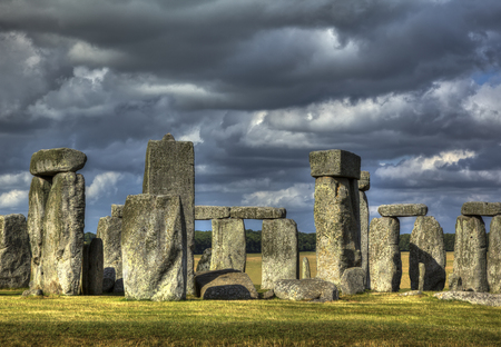 Close up of Stonehenge sunlit with dramatic clouds gathering photo