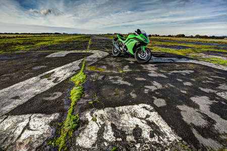 disused: Green sports motorcycle parked on disused airfield runway