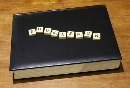 purposely: Game letter tiles purposely mis-spelling edukashun arranged on book