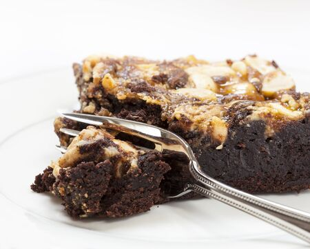 postre: Brownie de chocolate con miel y relleno tuerca se corta con un tenedor de postre Foto de archivo