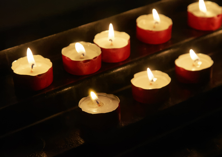 votive candle: Group of lit votive candles in church