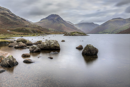 Wastwater looking towards Great Gable with stones in water long exposure Stock Photo