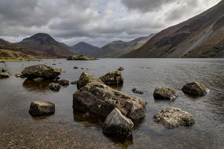 Wastwater looking towards Great Gable with stones in water Stock Photo