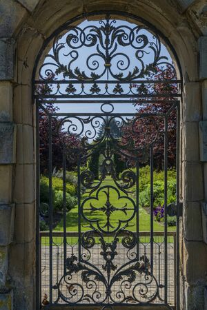 wrought iron gate leading to formal garden at stately home Фото со стока