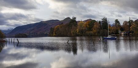 panorama of derwentwater in autumn towards borrowdale with yacht at anchor and boathouse from friars crag