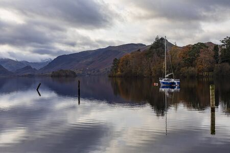 derwentwater in autumn looking towards borrowdale and castle crag with yacht at anchor