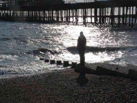 Figure on beach at Hastings East Sussex uk photo