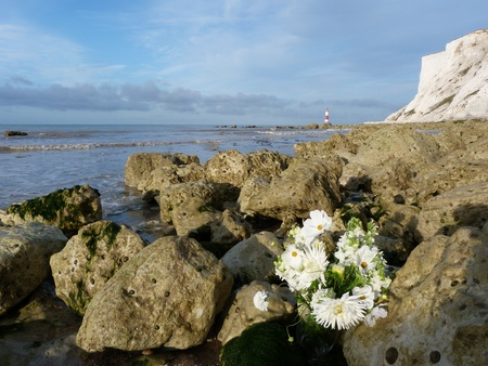 Lighthouse and Beach at Beachy Head with Memorial Flowers photo
