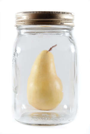 Ripe canning pear behind a glass mason jar on a white isolated background. Stock Photo - 7870883
