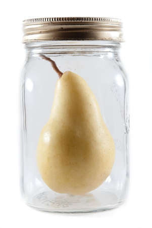 Ripe canning pear inside a a glass mason jar on a white isolated background Stock Photo - 7870884