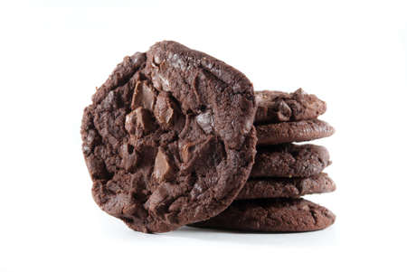 chocolate chips: Upright cookie against stack of double chocolate chip cookies on white isolated background.