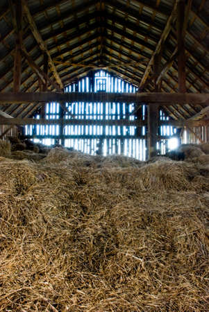 room door: Old wooden barn full of old hay with light shining through the wooden boards.