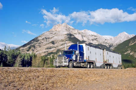 numberplate: a semi truck going up through the Canadian Rockies with motion blur