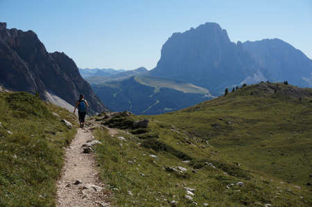 hiker walks on trail on to alp in the dolomite mountains Stock Photo