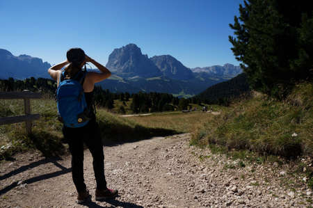 Hiker on Alp enjoys views of the Dolomites Mountains Stock Photo