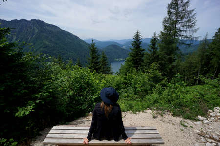 Happy and sporty hiker woman takes a rest and enjoys the view onto a beautiful lake / green trees around the lake / relax and meditation