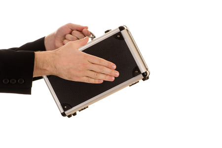 mans hand with sleeves of a black jacket holds for the handle the closed metal silver case and other hand lies a palm on a case