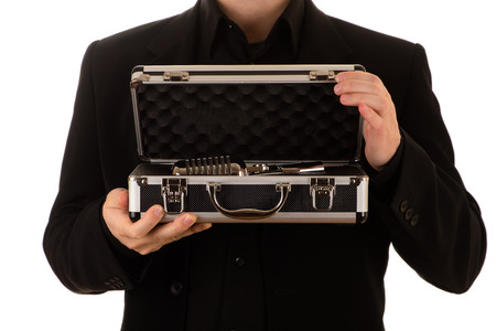 man in a black keeps an open metal case with a microphone inside Banco de Imagens