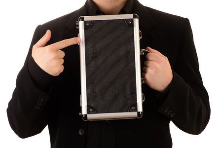 the case before: man in a black points a finger at a metal case Stock Photo