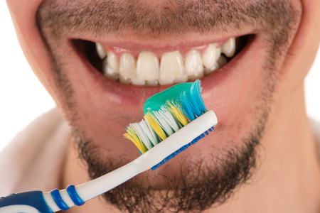 lower part of face of man with beard and mustache and white and blue toothbrush and white towel, closeup Banco de Imagens