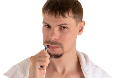 Portrait of an adult man cleaning his teeth with toothbrush and white towel on his shoulders looking at camera Banco de Imagens