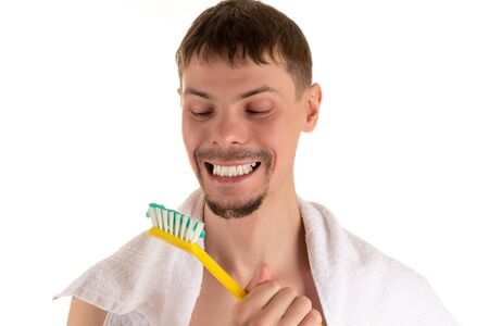 portrait of a man smiling broadly looking at a giant white toothbrush with toothpaste in his hand