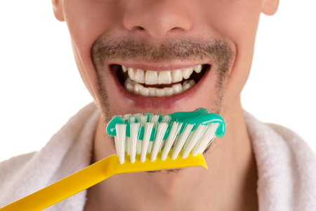 lower part of face of man with big yellow toothbrush and white towel on shoulders closeup