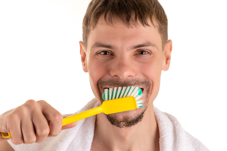 portrait of adult smiling man with big yellow toothbrush in hand and white towel on his shoulders