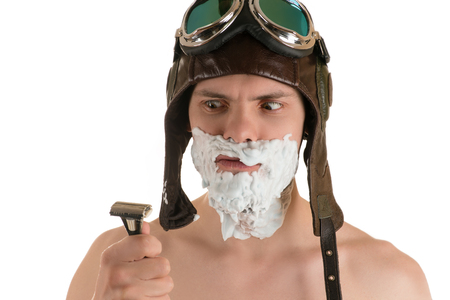 flight helmet: Portrait of an adult man with shaving foam on his face in flight helmet and flying goggles looking at razor in his hand