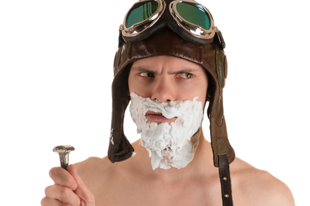 flight helmet: portrait looking in direction of man with shaving foam on his face in flight helmet and flying goggles and razor in his hand Stock Photo