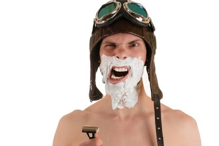 flight helmet: Portrait of screaming man with narrowed eyes with shaving foam on his face in flight helmet and flying goggles with razor in his hand