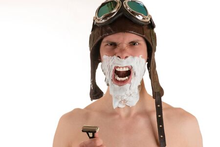 flight helmet: Portrait of screaming man with shaving foam on his face in flight helmet and flying goggles with razor in his hand