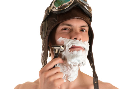 portrait of a man shaving with shaving foam on his face in a flight helmet and flying goggles with narrowed right eye