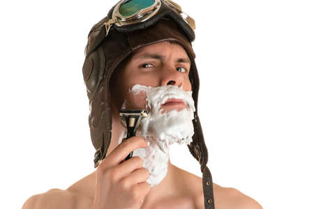 flight helmet: portrait of a man shaving with shaving foam on his face in a flight helmet and flying goggles arrogantly looking at the camera