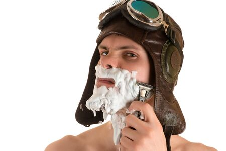 sternly: portrait of man shaving with shaving foam on his face in flight helmet and flying goggles looking sternly at camera