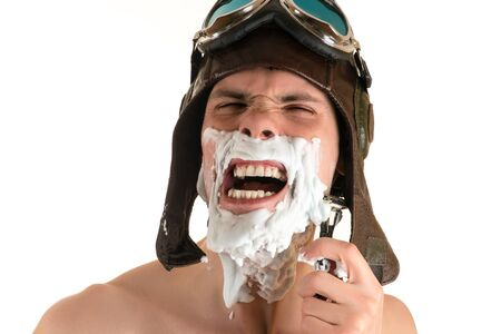 flight helmet: portrait screaming from pain shaving of man with shaving foam on his face in flight helmet and flying goggles