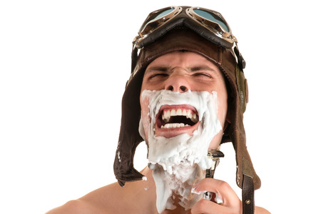 Portrait of a screaming man shaving with shaving foam on his face in flight helmet and flying goggles