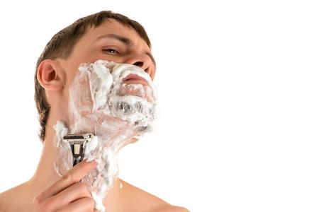 portrait of young caucasian male in shaving foam shaving sharp razor neck