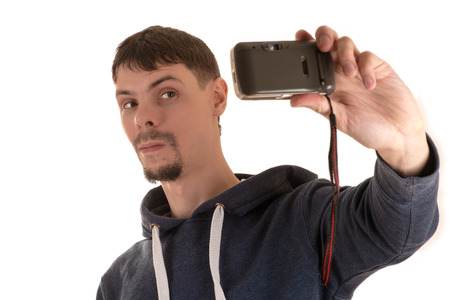 young man in gray jacket with hood holding with his left hand and takes pictures old camera itself
