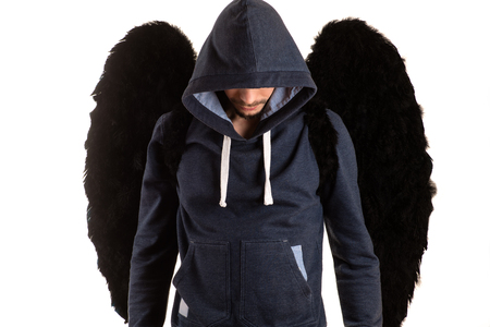 young man in gray jacket with his head in the hood standing with her hands on her back and black wings Banco de Imagens