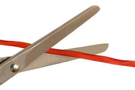 Scissors cut a thin red ribbon white background Banco de Imagens