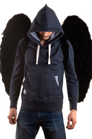 young man in gray jacket with hood thrown over his head and jeans standing with her hands on back and black wings Banco de Imagens