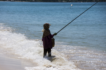 Fisherwoman with fishing rod standing by the ocean, Thailand